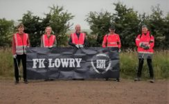 The team pose for a group photo with the FK Lowry banner